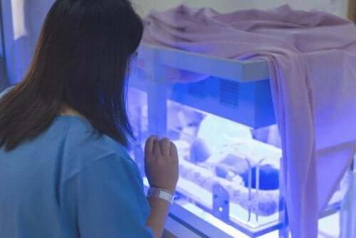 Kobieta patrząca na dziecko w inkubatorze