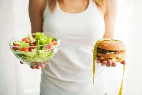 Kobieta trzymająca sałatkę i hamburgera - jak ochronić się przed otyłością