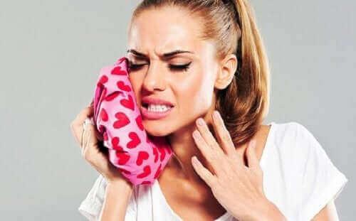 Kobieta przykłada zimny okład na ból zęba