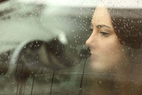 Smutna kobieta patrzy przez okno podczas deszczu