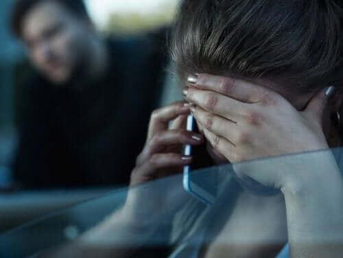 Załamana kobieta rozmawia przez telefon - zgłoszenie przemocy w rodzinie