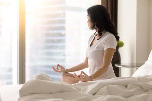 Kobieta medytująca na łóżku - jak wyrobić w sobie nawyk?