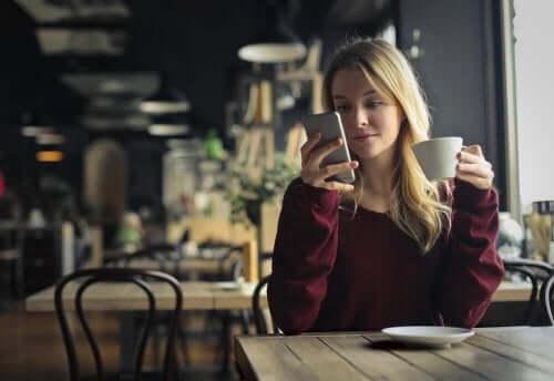 Kobieta pijąca kawę i patrząca na telefon