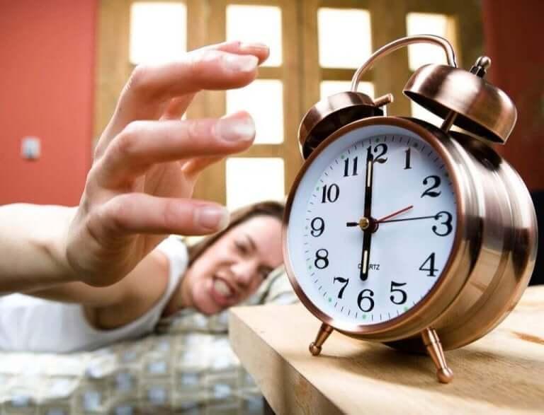 Kobieta sięgająca ze złością po budzik