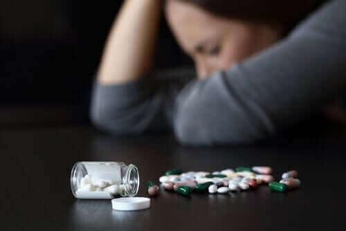 Kobieta śpiąca na stole z rozsypanym tabletkami - senność wywoływana przyjmowaniem leków