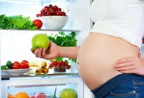 Kobieta w ciąży trzymająca jabłko - dieta w ciąży