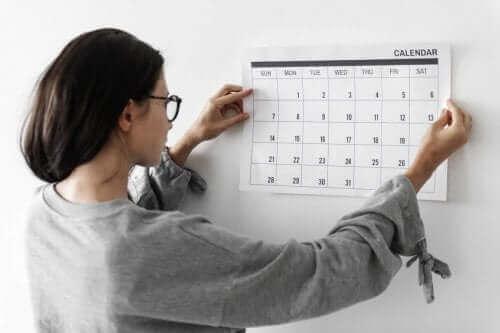 Kobieta wieszająca kalendarz na ścianie