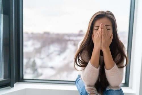 Kobieta zakrywająca twarz - zespół stresu pourazowego