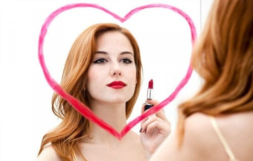 Kobieta rysuje serce szminką