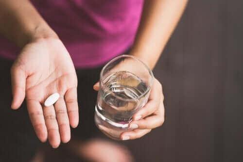 Kobieta trzymająca tabletkę i szklankę wody