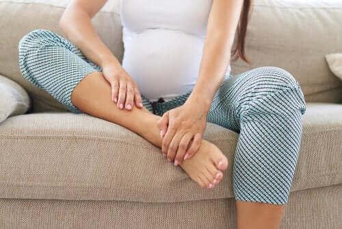 Kobieta w ciąży trzymająca się za kostkę - ból kości podczas ciąży