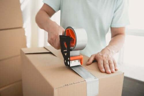Mężczyzna pakujący rzeczy do pudełka - jak zorganizować dom?
