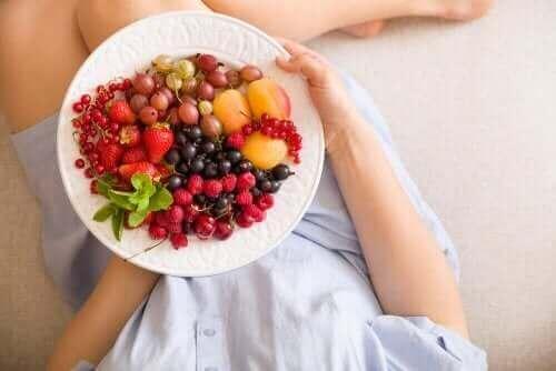 Kobieta w ciąży z talerzem owoców - jedzenie w ciąży