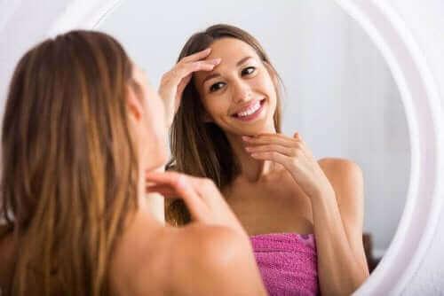 Uśmiechnięta kobieta oglądająca swoją twarz w lustrze - warto zmywać makijaż przed snem