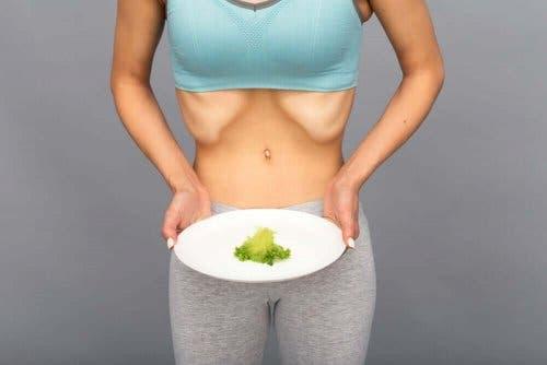 Wychudzona kobieta trzyma talerz z liściem sałaty