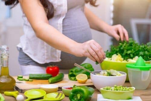 Kobieta w ciąży szykująca sałatkę - przyjmowanie kwasu foliowego w ciąży