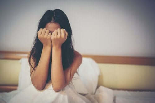 Płacząca kobieta w łóżku - znęcanie się psychiczne