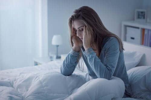 Zmęczona kobieta w łóżku - zaburzenia związane z bezsennością