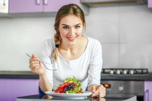 Kobieta z sałatką - co warto zrobić przed rozpoczęciem diety wegańskiej