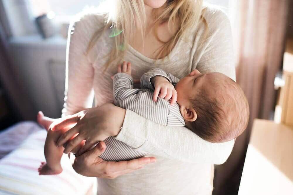 Mama trzymająca niemowlę - materiały na ubranka dla niemowląt