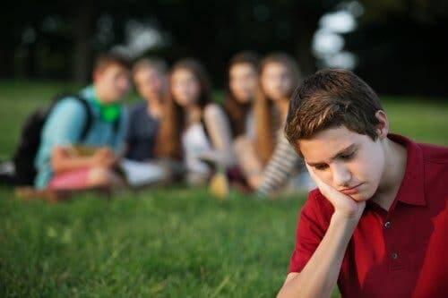 Siedzący sam nastolatek - presja równieśnicza