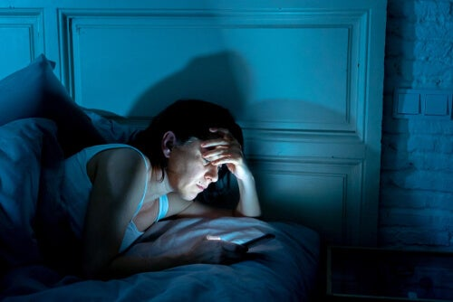 Kobieta z telefonem w łóżku