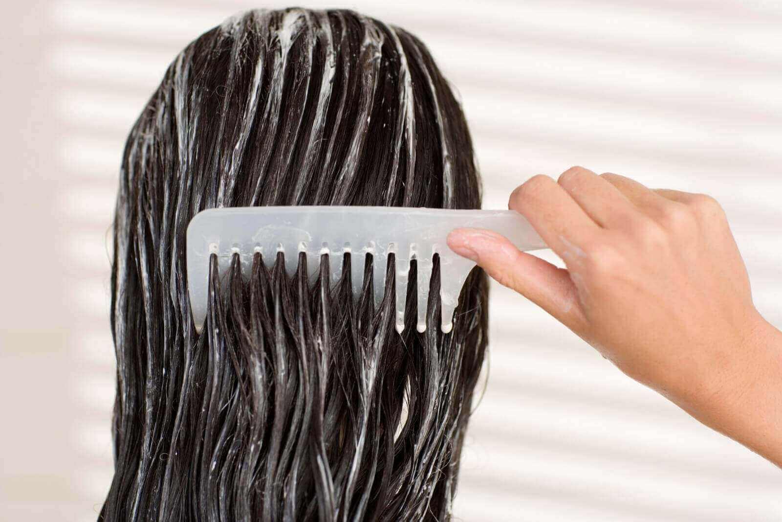Kobieta nakładająca maseczkę na włosy - pielęgnacja farbowanych włosów
