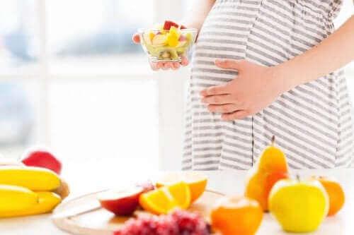 Kobieta w ciąży jedząca owoce