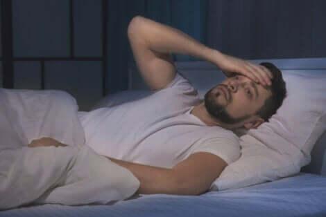Mężczyzna w łóżku cierpiący na bezsenność