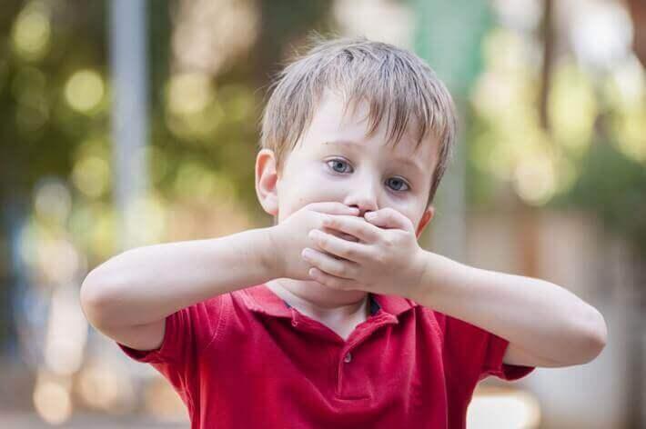 Chłopiec zasłaniający usta