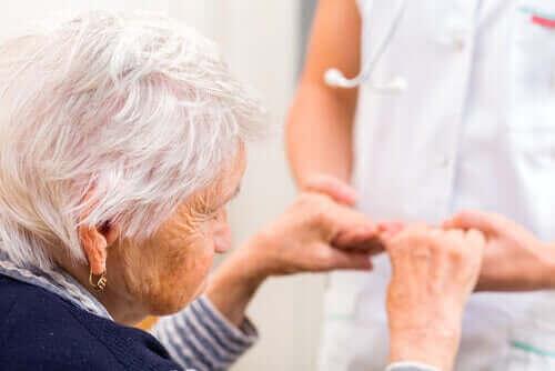 Starsza kobieta wstaje, trzymając za ręce opiekuna