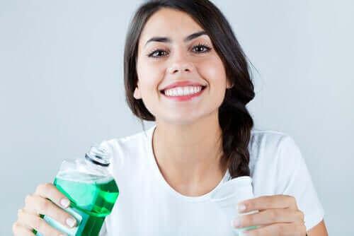 Kobieta z płynem do płukania jamy ustnej