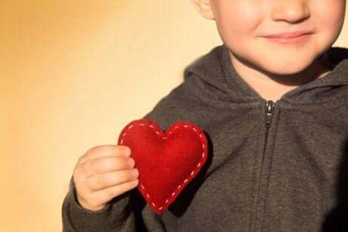 Dziecko trzyma serce uszyte z materiału