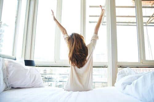Przeciągająca się kobieta na łóżku
