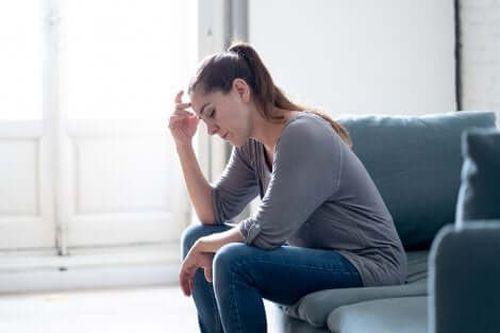 Zmartwiona kobieta siedzi na sofie z głową podpartą o rękę