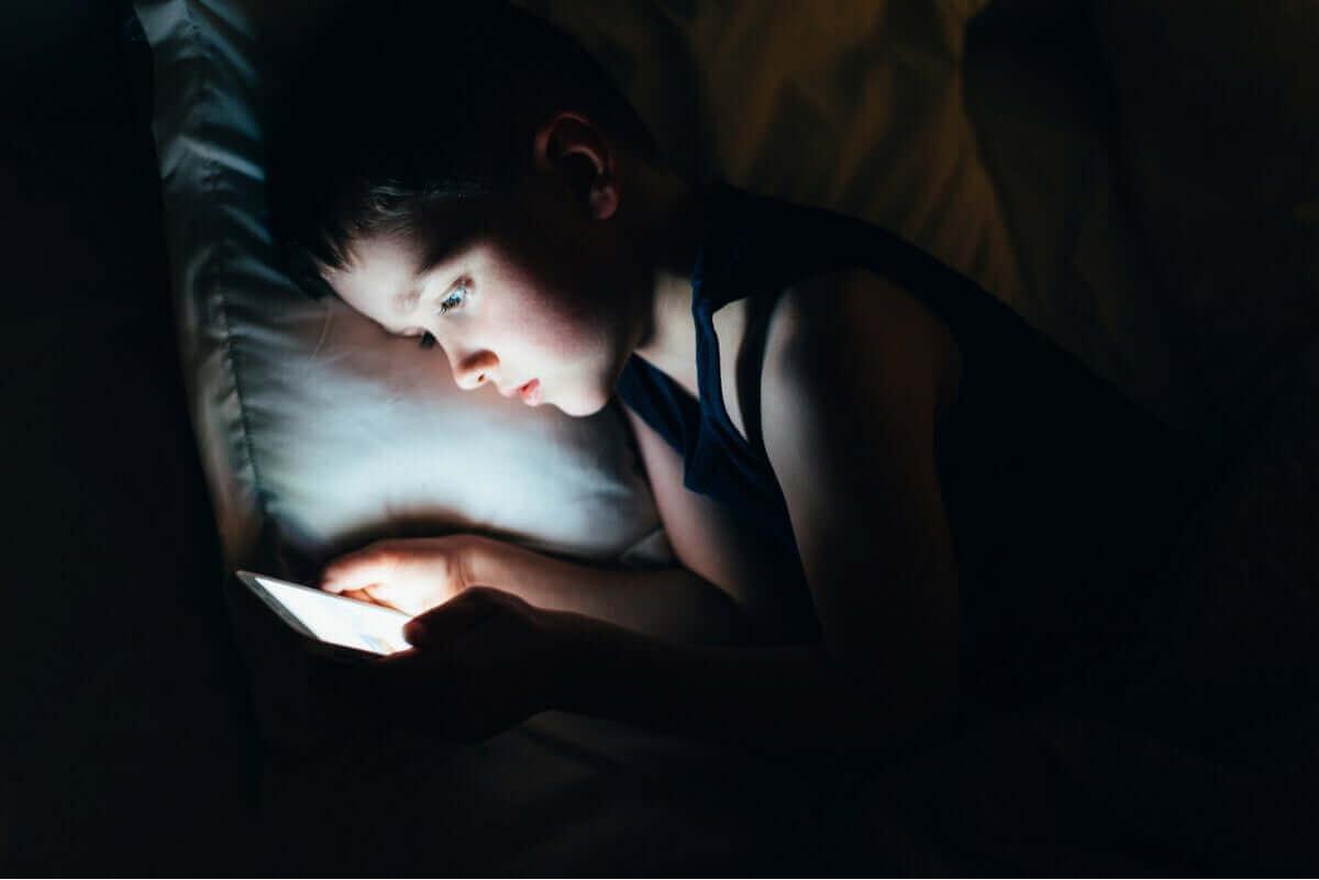 Chłopiec korzystający z telefonu w łóżku