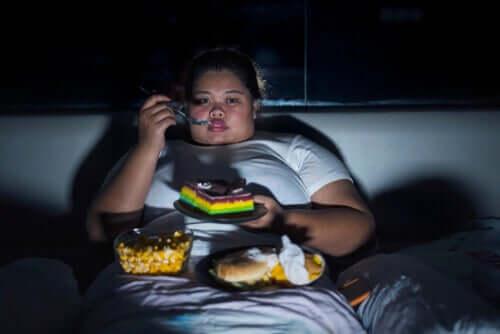 Otyła kobieta objadająca się ciastami