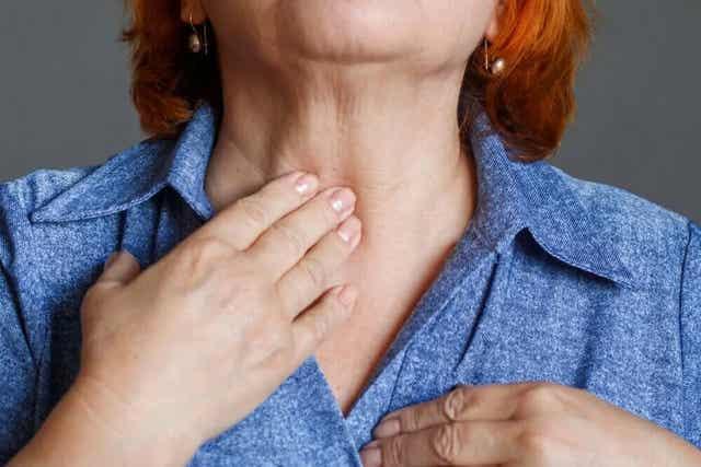 Kobieta dotykająca szyi