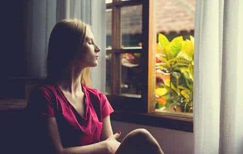 Kobieta wygląda przez okno - czy to wczesne objawy demencji?